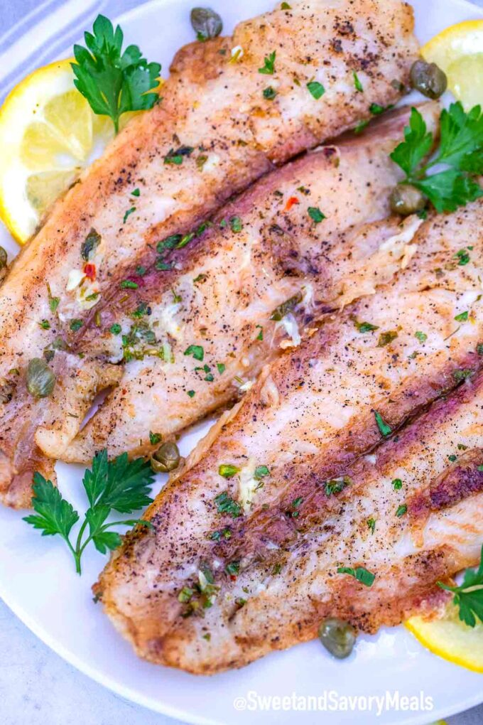 Swai fish fillets on a plate with lemon and parsley