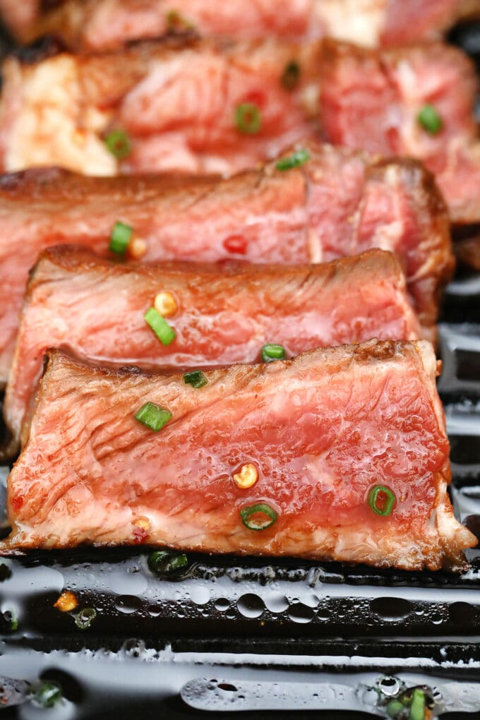 Picture of grilled steak topped with homemade asian marinade.
