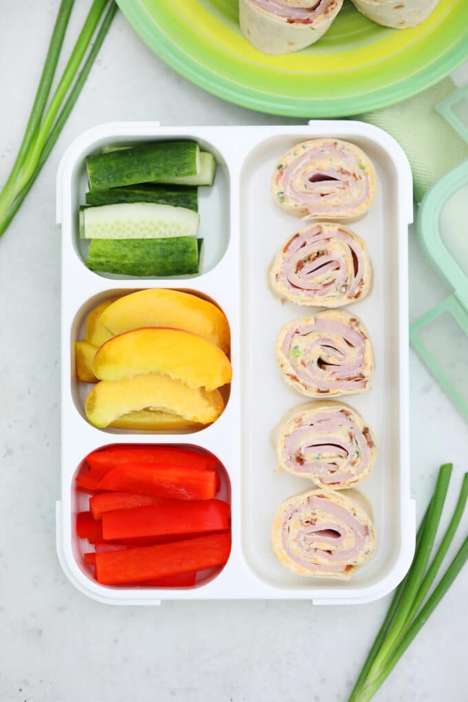 Picture of turkey pinwheels in with sliced cucumber and red bell peppers in a lunch box.