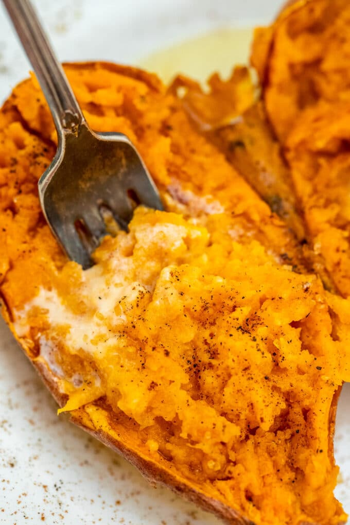 Picture of microwaved sweet potato garnished with butter.