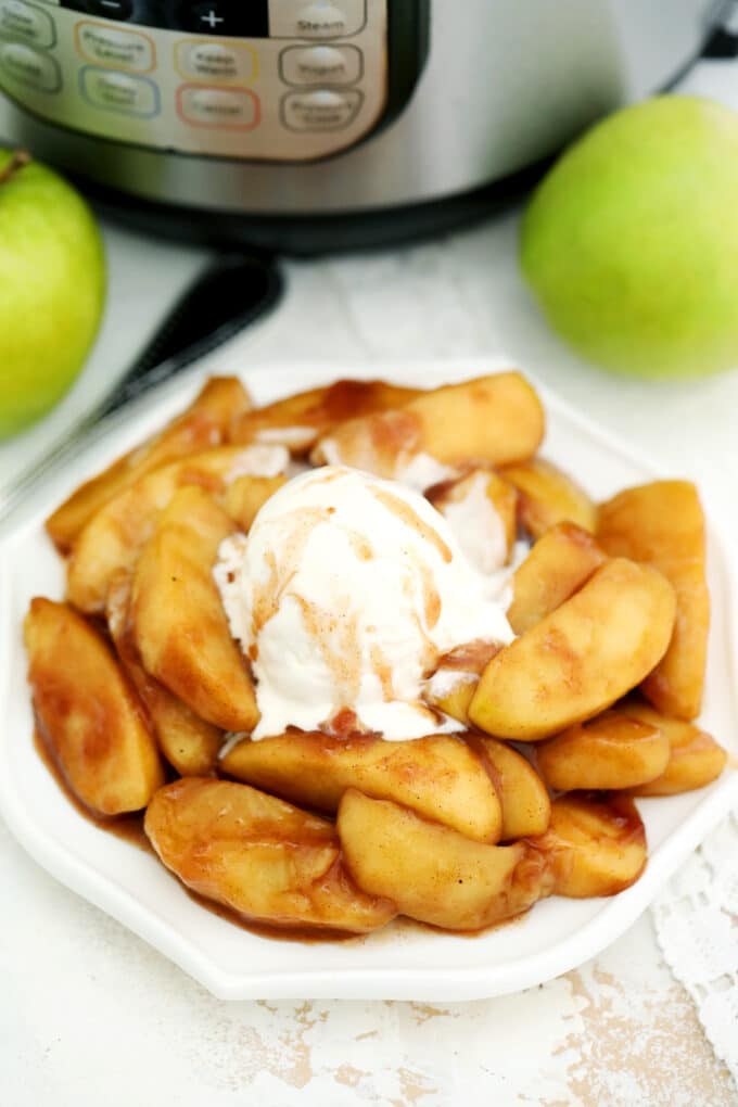 Image of cooked cinnamon apples topped with ice cream and caramel on a white plate.