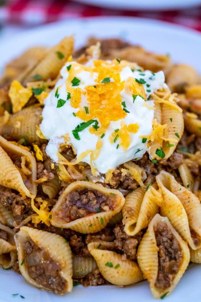 Photo of taco pasta garnished with sour cream and shredded cheese.