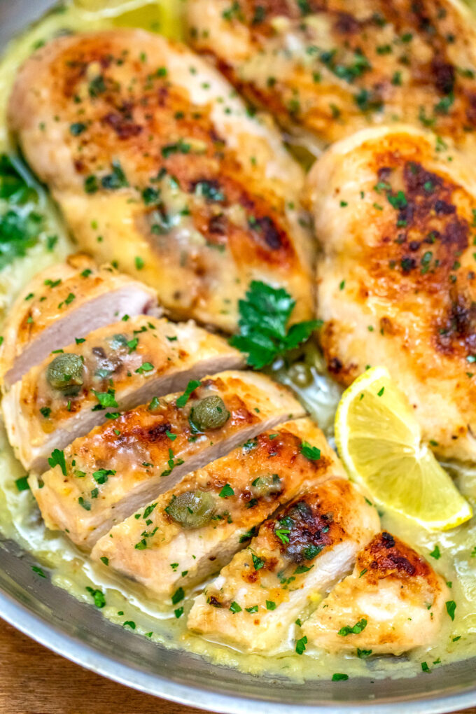 image of sliced chicken piccata breasts garnished with sliced lemon and parsley