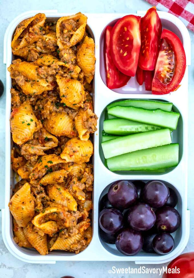 beef and shells in a lunch box with tomatoes cucumbers and blueberries