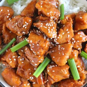 Mongolian chicken with rice and topped with green onions and sesame seeds