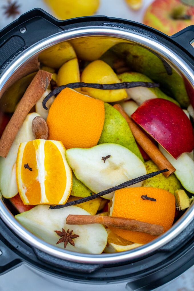 Instant Pot Apple Cider recipe is made with fresh apples, oranges, spices, and maple syrup. #applecider #instantpotrecipes #pressurecookerrecipes #sweetandsavorymeals #drinks