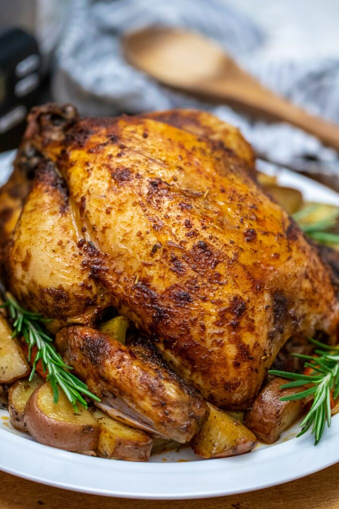 Photo of slow cooker whole chicken with rosemary over potatoes.