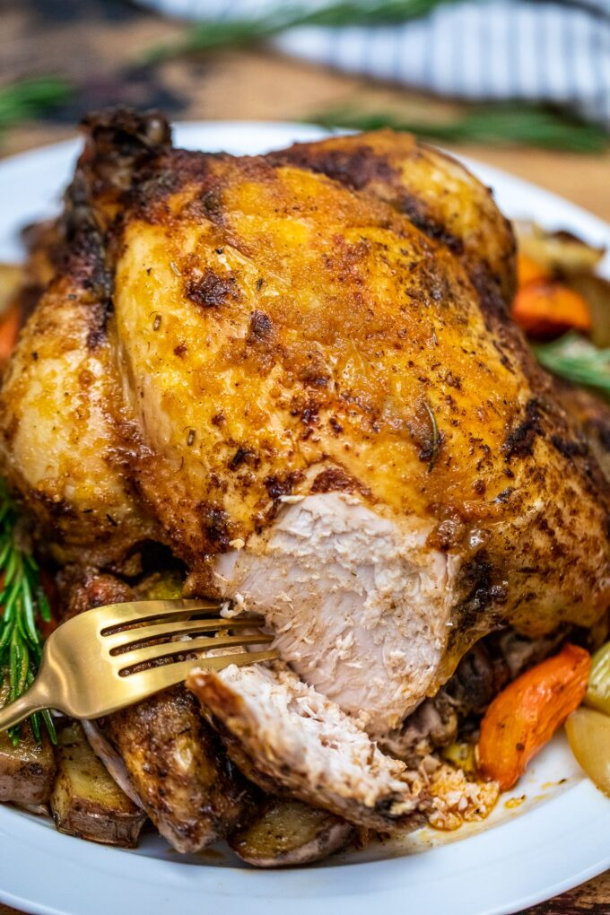 Juicy whole chicken with vegetable cooked in the slow cooker.