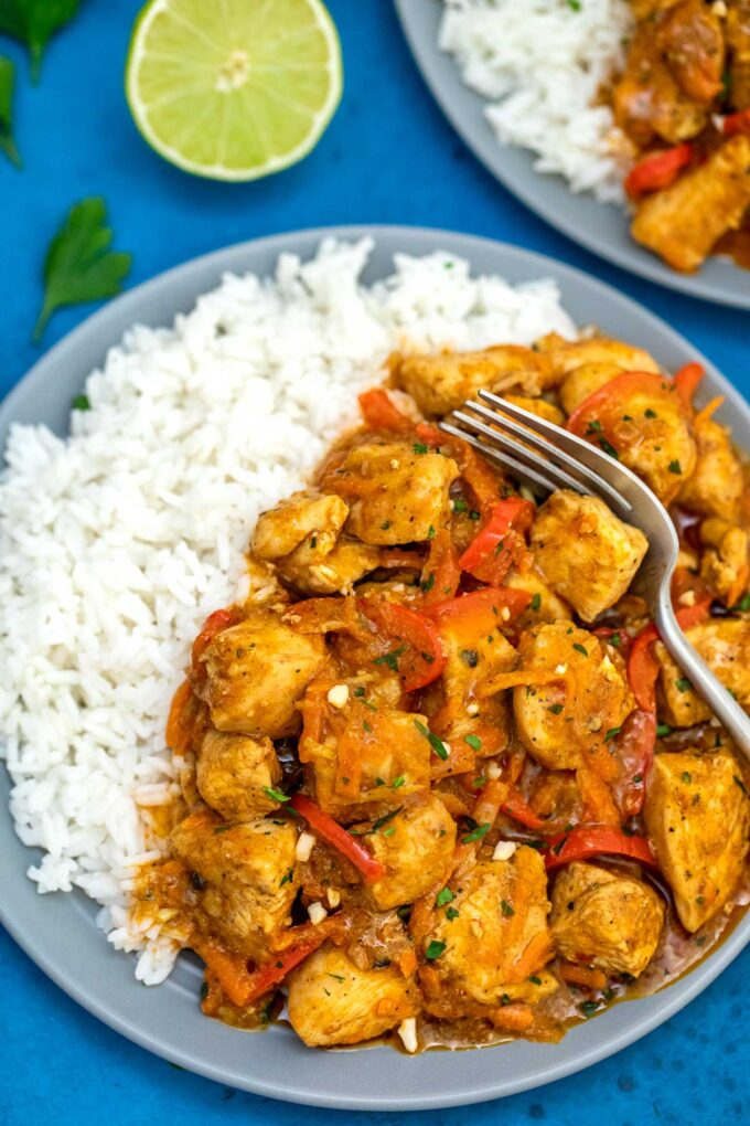 image of coconut curry chicken plated with lime on the side