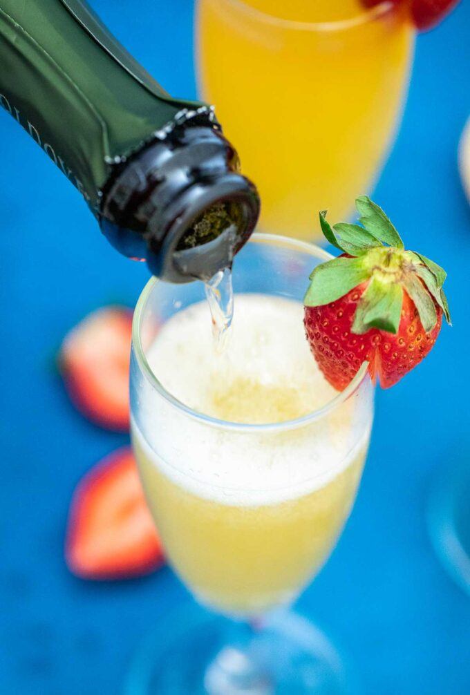 image of sparkling wine being added to a mimosa