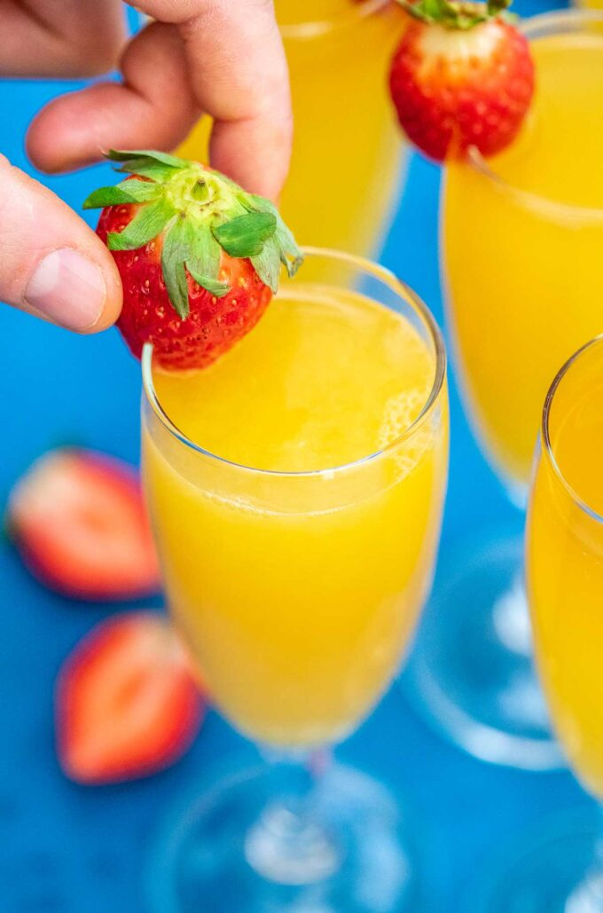photo of strawberry added to a flute of mimosa