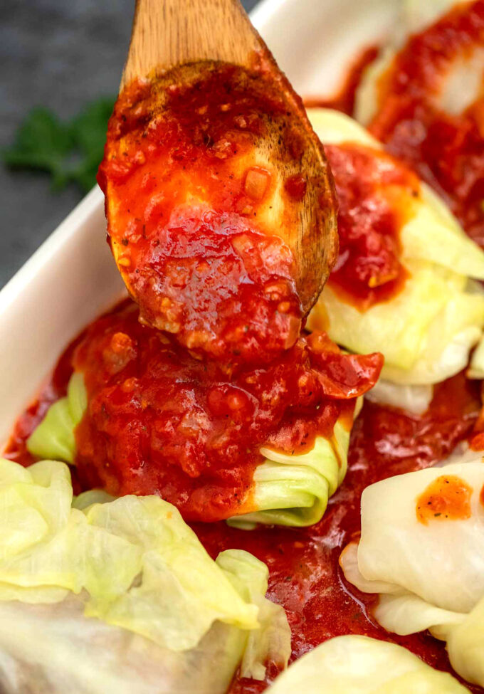 photo of stuffed cabbage rolls uncooked with tomato sauce