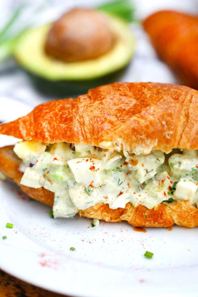 Photo of avocado egg salad on a croissant.