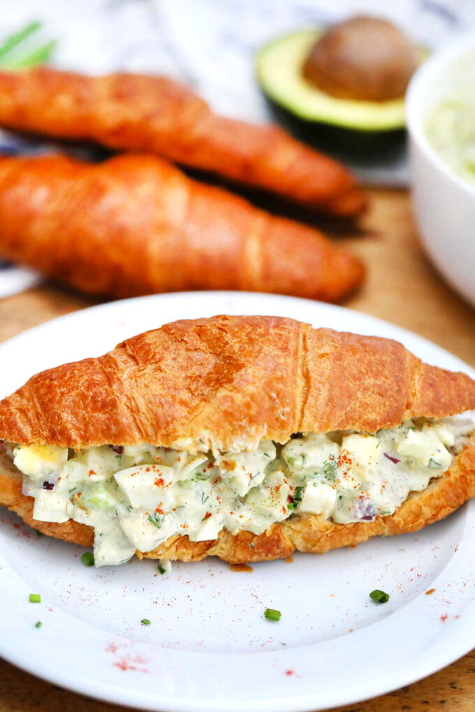 Photo of egg salad made with avocado on a croissant.