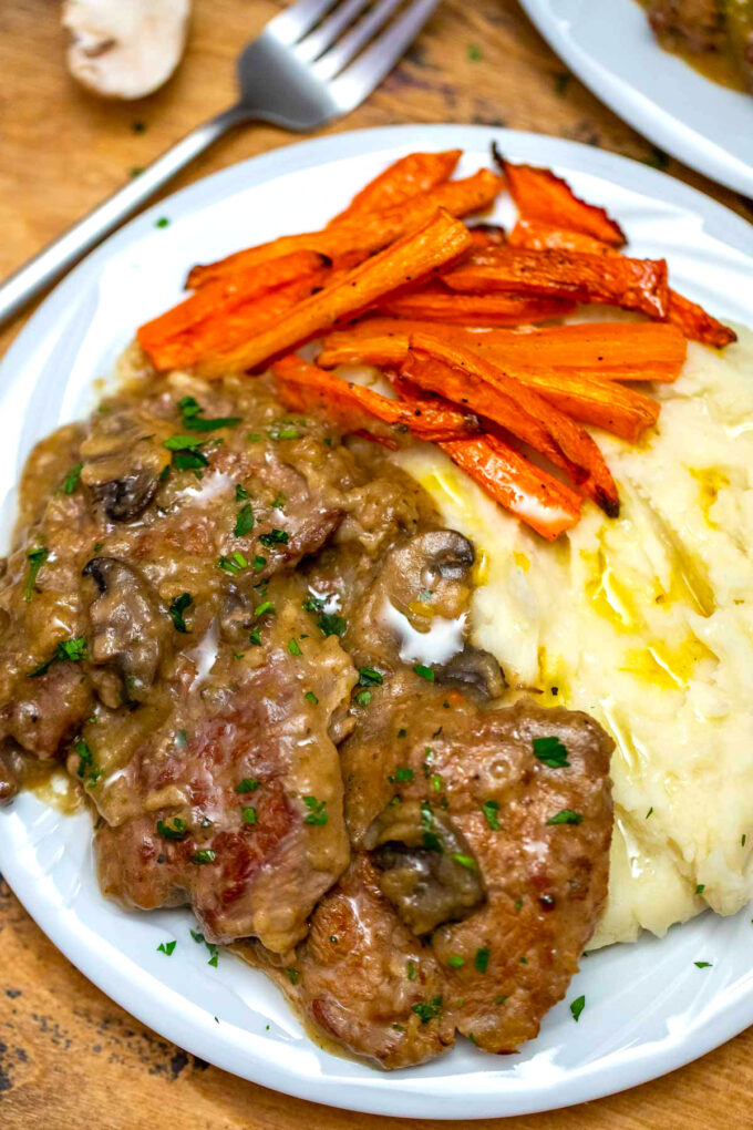 image of crockpot Swiss steak with gravy and mashed potatoes