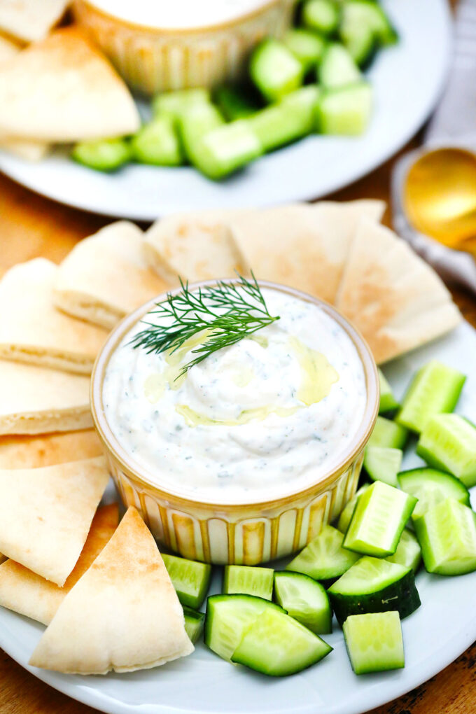 photo of tzatziki sauce with pitas and cucumbers