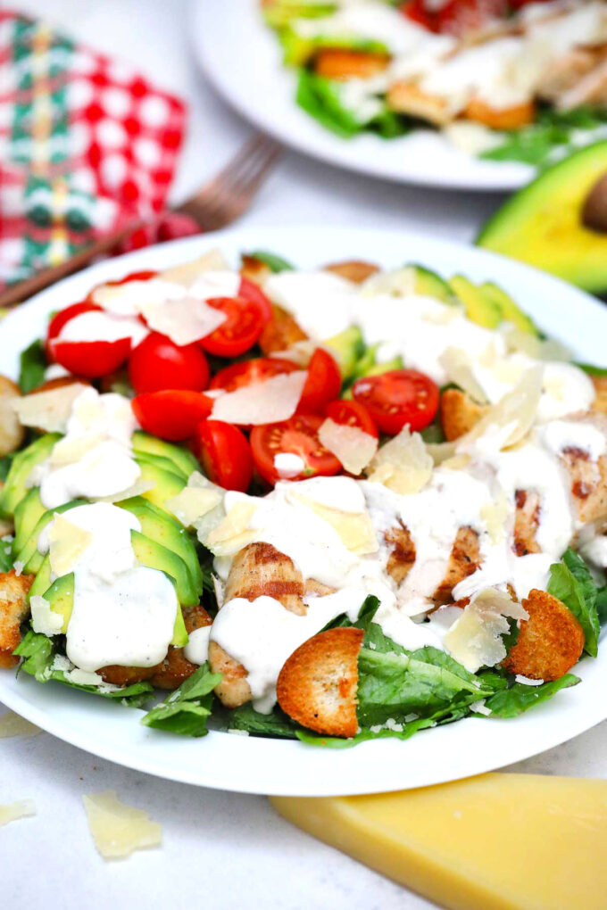 Photo of homemade avocado chicken caesar salad with Caesar Dressing and shaved parmesan.