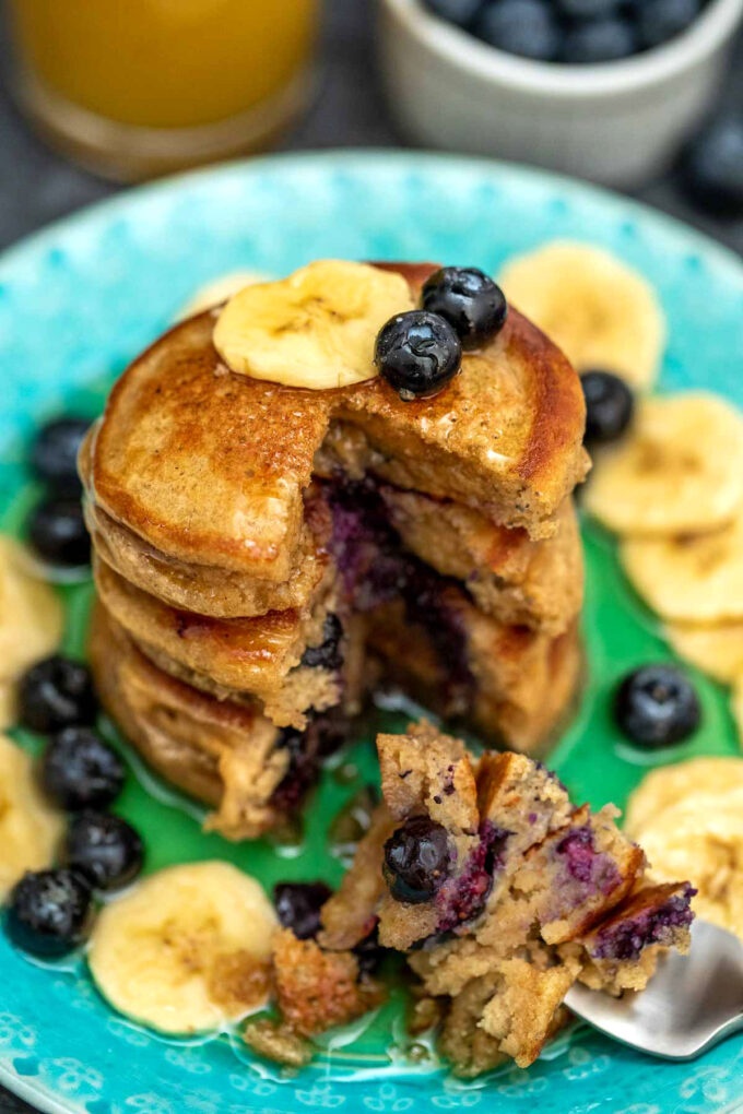 Photo of blueberry oatmeal pancakes with fresh berries.