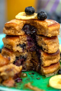 Picture of blueberry oatmeal pancakes topped with banana slices.