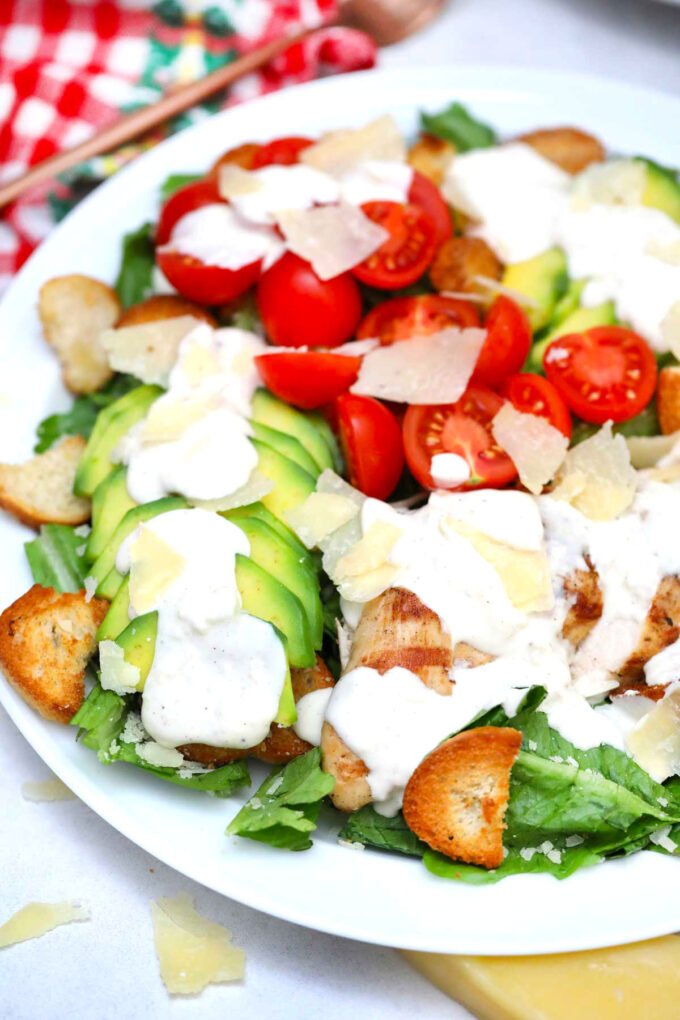 Photo of avocado chicken caesar salad on a white plate.