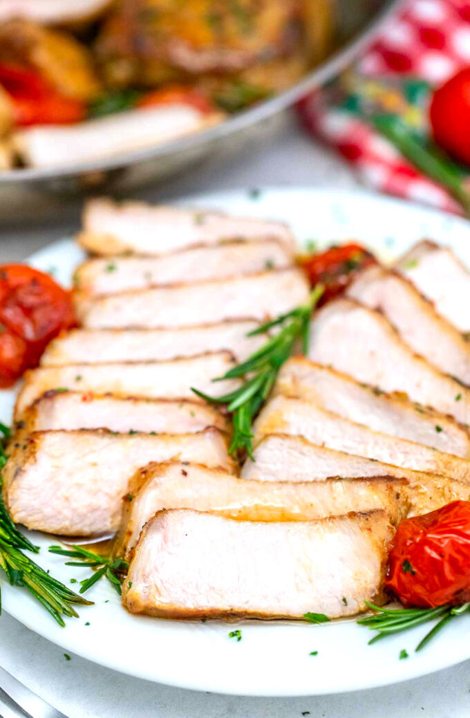Picture of sliced juicy pork chops with roasted tomatoes and rosemary.