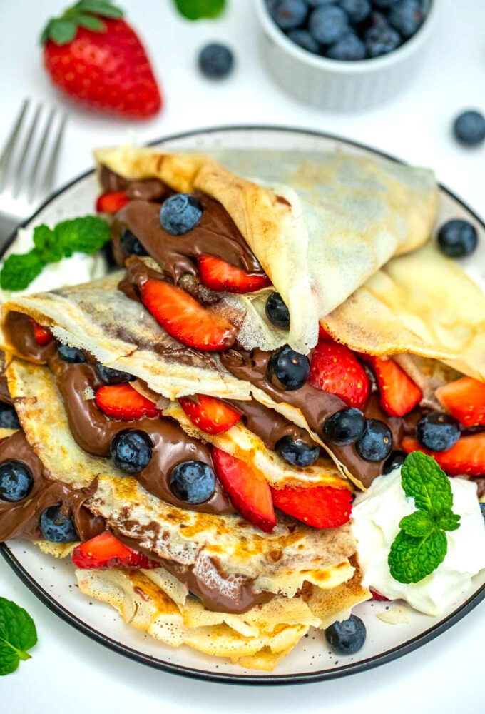 Image of crepes served with berries and chocolate filling.