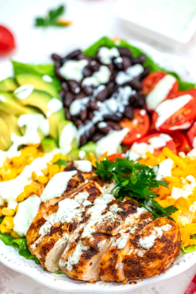 Photo of grilled chicken southwest salad with corn beans tomatoes avocado and cheese.