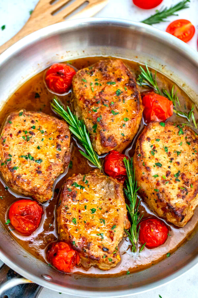 Photo of pan seared pork chops with tomatoes and rosemary.