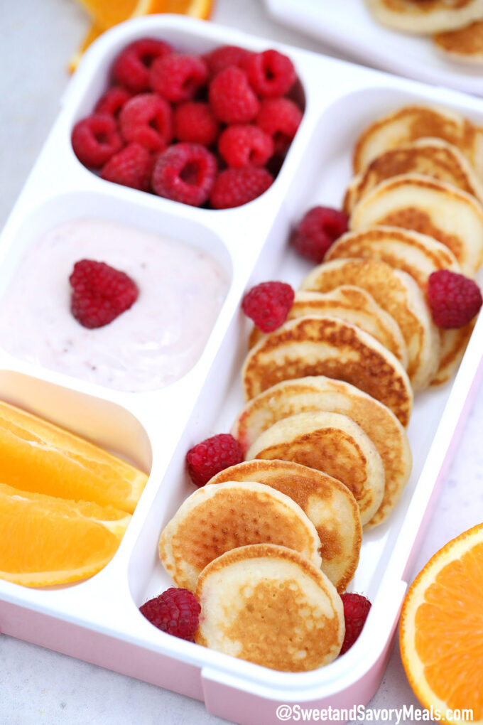 Photo of a lunch box with mini pancakes.