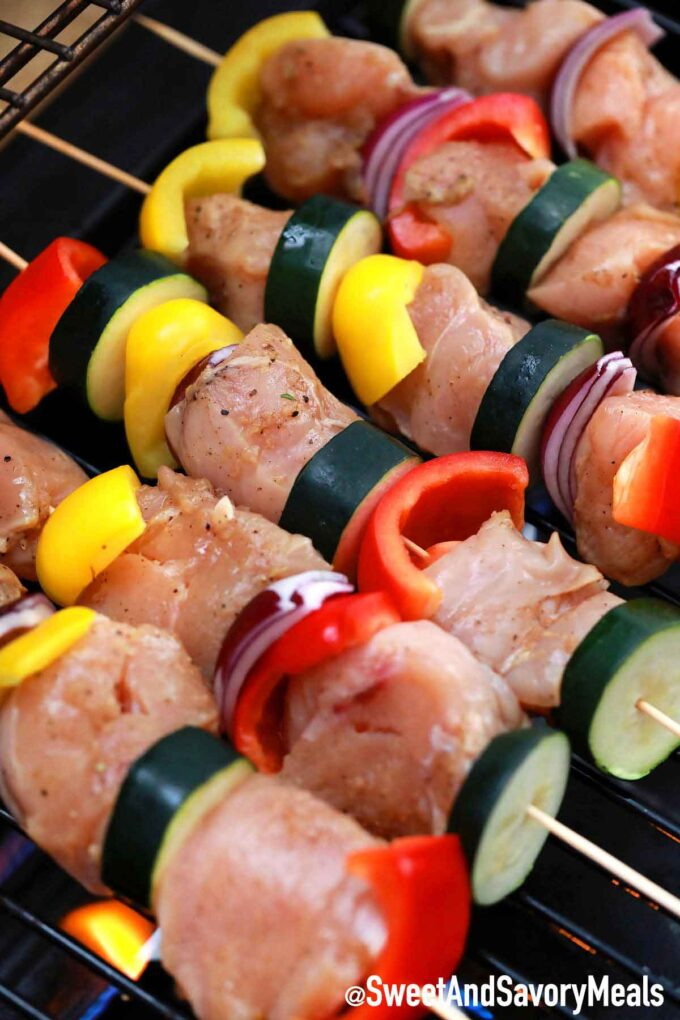 Chicken skewers and veggies on the grill.