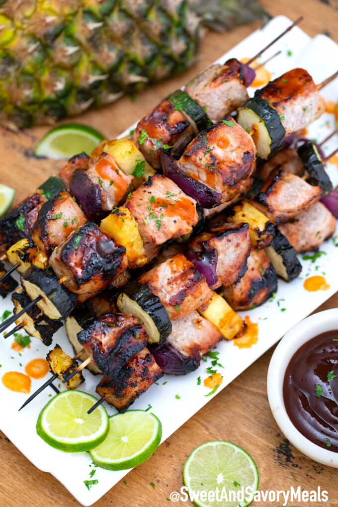 Grilled pork skewers on a white plate.