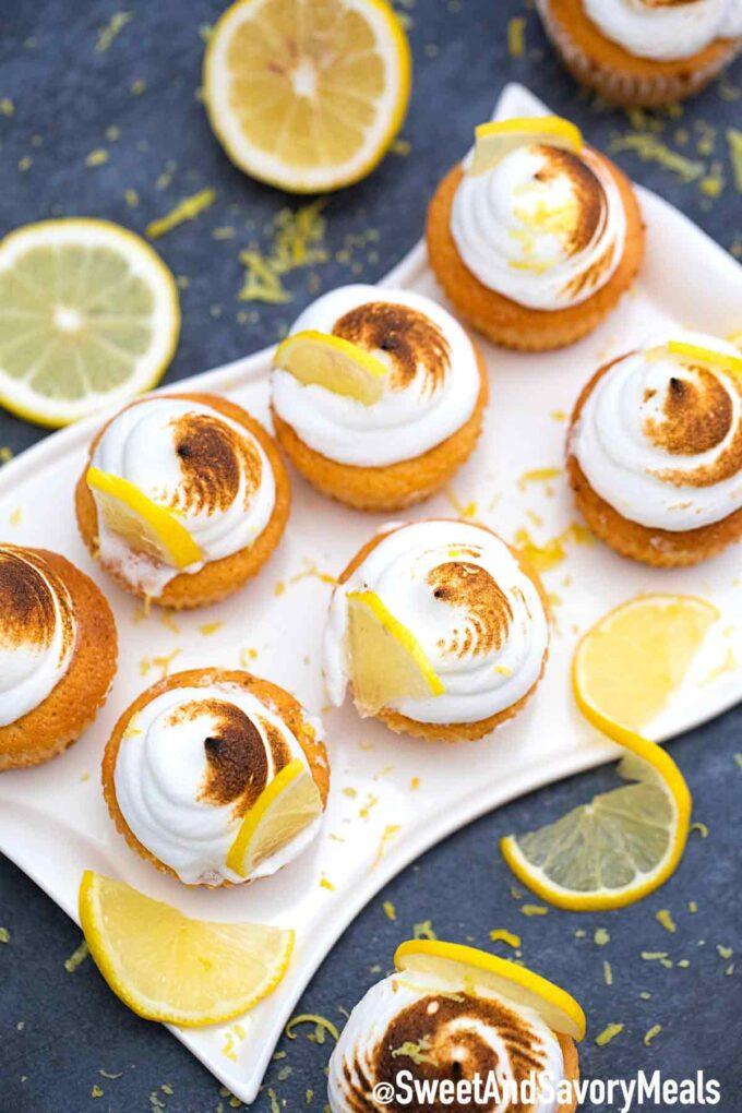 Lemon meringue cupcakes on a white plate with lemons.