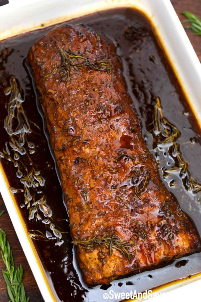 Roasted pork loin in balsamic sauce in a casserole dish with fresh herbs