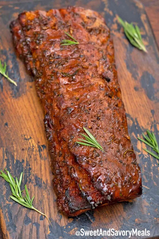 Freshly oven baked pork loin with rosemary on a wooden board