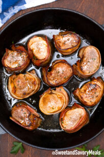bacon wrapped pork medallions in a cast iron skillet