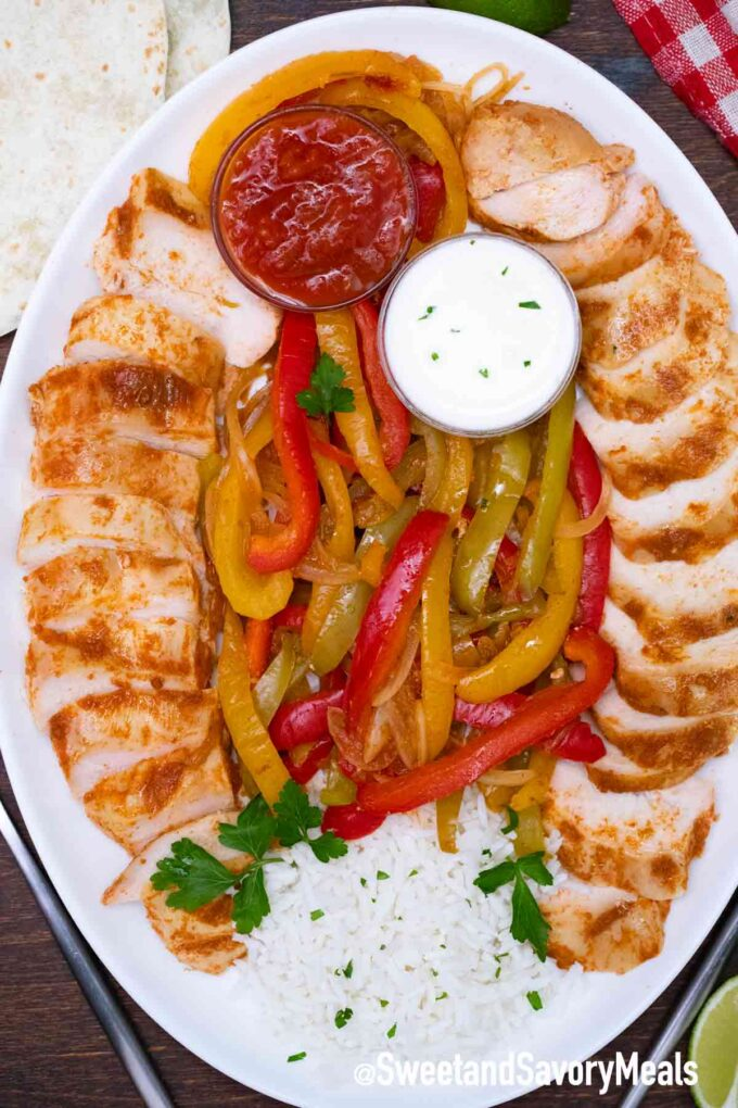 slow cooker chicken fajitas on a plate with rice sour cream and salsa