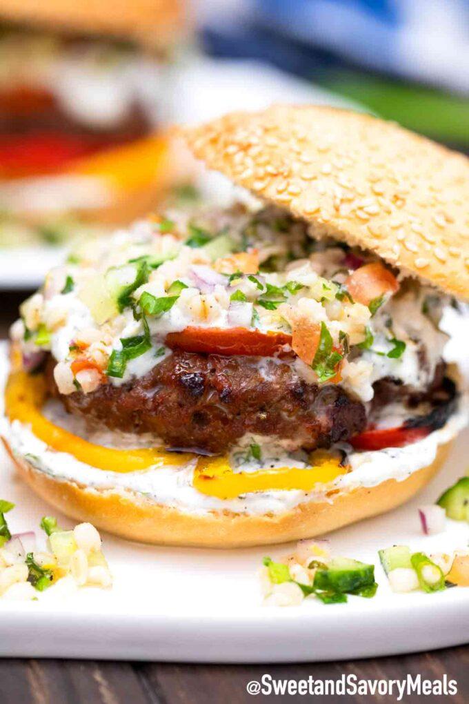 lamb burgers with yogurt sauce and red onion on a bun