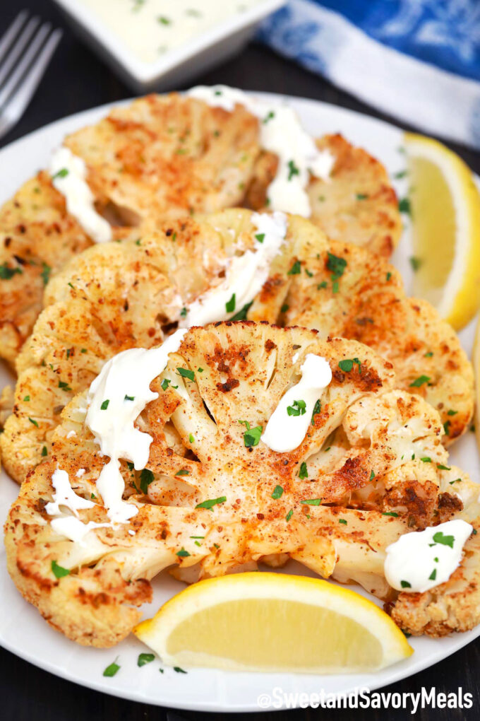 cauliflower steaks on a plate with lemon and white sauce