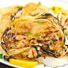 teriyaki cabbage steaks on a plate with lemon wedges