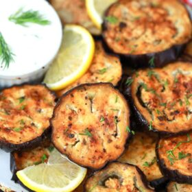 air fryer eggplant on a plate with tzatziki sauce