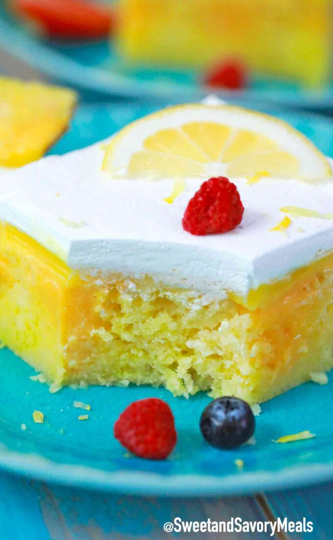 lemon poke cake topped with whipped cream