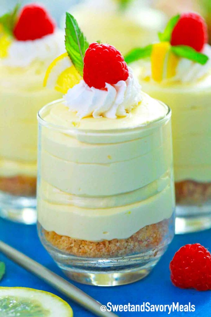 lemon mousse topped with whipped cream raspberries and mint
