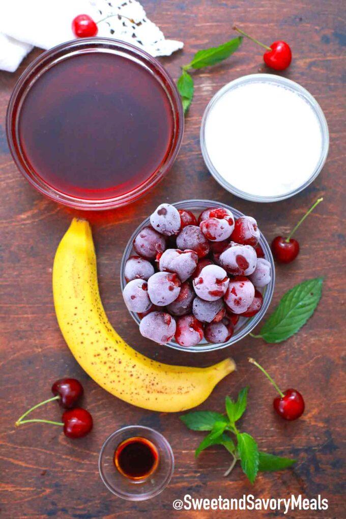 cherry smoothie ingredients on a table, banana, frozen cherries, yogurt, cherry juice and vanilla extract