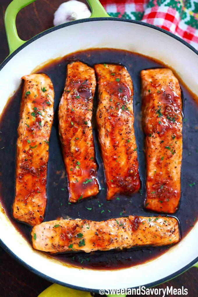 honey garlic salmon fillets in sauce in a green pan