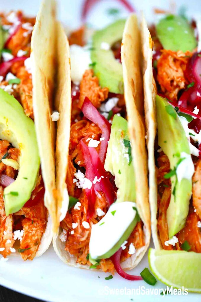 Chicken Tinga tacos with red onions and avocado in a flour tortilla