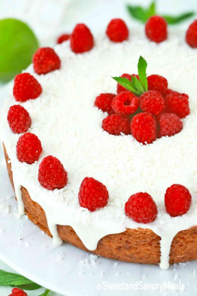 slow cooker raspberry cake with frosting and fresh raspberries