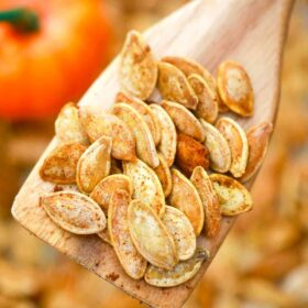 roasted pumpkin seeds on a wooden spoon